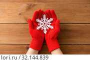 hands in red woollen gloves holding big snowflake. Стоковое фото, фотограф Syda Productions / Фотобанк Лори