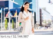 Купить «happy smiling asian woman with headphones in city», фото № 32144987, снято 13 июля 2019 г. (c) Syda Productions / Фотобанк Лори