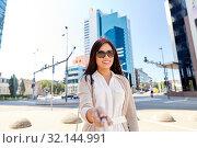 Купить «asian woman taking picture by selfie stick in city», фото № 32144991, снято 13 июля 2019 г. (c) Syda Productions / Фотобанк Лори