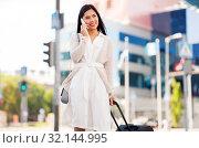 Купить «woman with travel bag calling on cellphone in city», фото № 32144995, снято 13 июля 2019 г. (c) Syda Productions / Фотобанк Лори