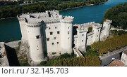 Купить «Aerial view of medieval fortified Chateau de Tarascon and Rhone river at sunny day», видеоролик № 32145703, снято 24 октября 2018 г. (c) Яков Филимонов / Фотобанк Лори