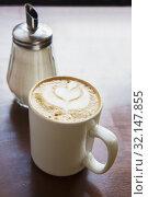 Купить «Cappuccino coffee in cup and sugar bowl», фото № 32147855, снято 29 июля 2016 г. (c) Юрий Бизгаймер / Фотобанк Лори