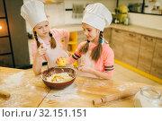 Купить «Little girls cooks in caps rubs lemon to the bowl», фото № 32151151, снято 30 марта 2019 г. (c) Tryapitsyn Sergiy / Фотобанк Лори