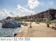 Купить «View of the promenade with hotels and fishing boats, the Black Sea resort of Nessebar», фото № 32151555, снято 26 июня 2019 г. (c) Юлия Бабкина / Фотобанк Лори