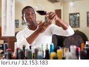 Купить «Confident african american male winemaker inspecting quality of red wine, checking it in wine store», фото № 32153183, снято 1 августа 2019 г. (c) Яков Филимонов / Фотобанк Лори