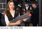 Купить «Fine woman and her colleagues in laser tag room», фото № 32154595, снято 4 апреля 2019 г. (c) Яков Филимонов / Фотобанк Лори
