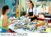Portrait of friendly female fishmonger showing raw European bass to woman behind counter of seafood store. Стоковое фото, фотограф Яков Филимонов / Фотобанк Лори