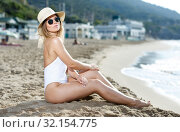 Купить «Sexy girl in swimsuit and sunglasses sitting at sand at sea shore», фото № 32154775, снято 10 июля 2018 г. (c) Яков Филимонов / Фотобанк Лори