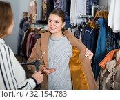 Купить «Women trying coat in clothing boutique», фото № 32154783, снято 6 декабря 2018 г. (c) Яков Филимонов / Фотобанк Лори