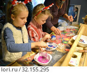 Дети обсыпают елочные игрушки блестками. Детский мастер-класс в мастерской (2018 год). Редакционное фото, фотограф Ирина Борсученко / Фотобанк Лори