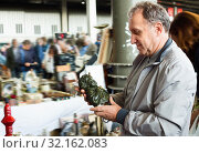 Positive elderly man choosing interesting souvenirs at traditional flea market. Стоковое фото, фотограф Яков Филимонов / Фотобанк Лори