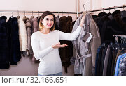 Купить «woman choosing sheepskin coat in women's cloths store», фото № 32166651, снято 23 февраля 2020 г. (c) Яков Филимонов / Фотобанк Лори