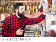 Купить «Young male customer examining sausages in butcher's shop», фото № 32166707, снято 16 ноября 2016 г. (c) Яков Филимонов / Фотобанк Лори