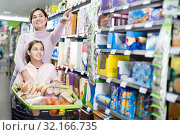 Купить «Woman with girl looking for food in supermarket», фото № 32166735, снято 5 января 2017 г. (c) Яков Филимонов / Фотобанк Лори