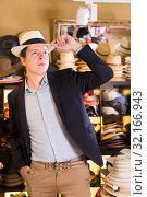 Купить «portrait of smiling guy try on bucket hat at store», фото № 32166943, снято 2 мая 2017 г. (c) Яков Филимонов / Фотобанк Лори
