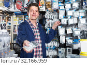Smiling worker in hardware store is trading sockets. Стоковое фото, фотограф Яков Филимонов / Фотобанк Лори