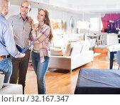 Купить «Seller offering family couple to choose furniture», фото № 32167347, снято 16 мая 2017 г. (c) Яков Филимонов / Фотобанк Лори