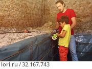 Купить «Father and son preparing framework for concrete», фото № 32167743, снято 10 июня 2018 г. (c) Сергей Новиков / Фотобанк Лори