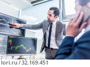 Купить «Businessmen trading stocks online. Stock brokers looking at graphs, indexes and numbers on multiple computer screens. Colleagues in discussion in traders office. Business success concept.», фото № 32169451, снято 9 июля 2020 г. (c) easy Fotostock / Фотобанк Лори