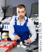Купить «Male worker picking up color of car upholstery», фото № 32170759, снято 4 апреля 2018 г. (c) Яков Филимонов / Фотобанк Лори