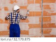 Купить «Workman is plastering the wall at the place», фото № 32170875, снято 6 марта 2019 г. (c) Яков Филимонов / Фотобанк Лори