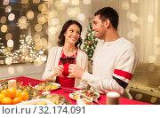 Купить «happy couple drinking red wine at christmas dinner», фото № 32174091, снято 11 января 2018 г. (c) Syda Productions / Фотобанк Лори