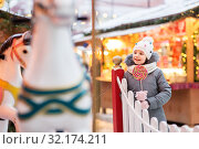 Купить «girl with lollipop at christmas market», фото № 32174211, снято 4 января 2019 г. (c) Syda Productions / Фотобанк Лори