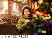 Купить «happy boy with cup of tea at christmas market», фото № 32174215, снято 4 января 2019 г. (c) Syda Productions / Фотобанк Лори