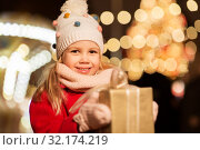 Купить «happy girl with gift box at christmas market», фото № 32174219, снято 4 января 2019 г. (c) Syda Productions / Фотобанк Лори