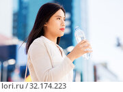 Купить «asian woman drinking water from bottle in city», фото № 32174223, снято 13 июля 2019 г. (c) Syda Productions / Фотобанк Лори