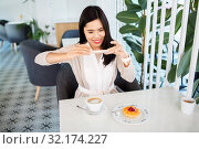 Купить «woman photographing coffee by smartphone at cafe», фото № 32174227, снято 13 июля 2019 г. (c) Syda Productions / Фотобанк Лори