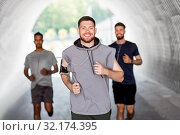 male friends with earphones running outdoors. Стоковое фото, фотограф Syda Productions / Фотобанк Лори
