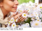 Купить «close up of happy woman smelling chamomile flowers», фото № 32174463, снято 12 июля 2019 г. (c) Syda Productions / Фотобанк Лори