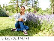 Купить «young woman and lavender flowers at summer garden», фото № 32174471, снято 12 июля 2019 г. (c) Syda Productions / Фотобанк Лори