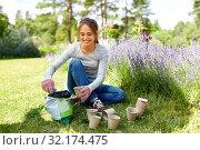 Купить «woman filling pots with soil at summer garden», фото № 32174475, снято 12 июля 2019 г. (c) Syda Productions / Фотобанк Лори