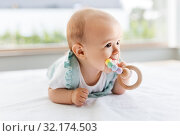 Купить «baby girl on white blanket chewing wooden rattle», фото № 32174503, снято 15 августа 2019 г. (c) Syda Productions / Фотобанк Лори