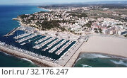 Купить «Picturesque aerial view of Mediterranean coastal town of Torredembarra with yachts moored in harbor, Tarragona, Spain», видеоролик № 32176247, снято 18 марта 2019 г. (c) Яков Филимонов / Фотобанк Лори