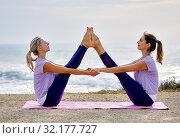 Купить «Women doing yoga exercise wide legged boat pose near the sea», фото № 32177727, снято 9 июня 2019 г. (c) Alexander Tihonovs / Фотобанк Лори