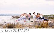 Women practising yoga do Side Angle Pose or Parivrtta Parsvakonasana outdoors. Стоковое фото, фотограф Alexander Tihonovs / Фотобанк Лори