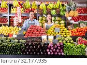 Купить «Man and woman sellers standing near vegetables and fruits», фото № 32177935, снято 19 октября 2019 г. (c) Яков Филимонов / Фотобанк Лори