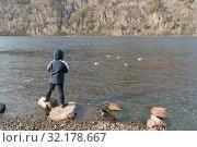Купить «Мальчик стоит на камнях, на берегу реки Енисей и смотрит на диких уток, плавающих в воде», фото № 32178667, снято 6 апреля 2019 г. (c) Светлана Попова / Фотобанк Лори