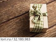 Купить «Simple wrapped gift on wooden table», фото № 32180983, снято 13 августа 2019 г. (c) Wavebreak Media / Фотобанк Лори