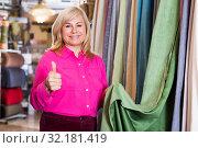 Купить «Woman seller showing curtain and holding thumb up», фото № 32181419, снято 17 января 2018 г. (c) Яков Филимонов / Фотобанк Лори