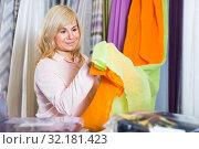 Купить «Mature woman customer choosing color curtains», фото № 32181423, снято 17 января 2018 г. (c) Яков Филимонов / Фотобанк Лори
