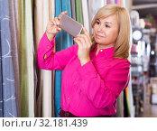 woman choosing curtains and using phone. Стоковое фото, фотограф Яков Филимонов / Фотобанк Лори