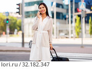 Купить «woman with travel bag calling on cellphone in city», фото № 32182347, снято 13 июля 2019 г. (c) Syda Productions / Фотобанк Лори