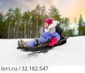 Купить «little kids sliding on sled down hill in winter», фото № 32182547, снято 10 февраля 2018 г. (c) Syda Productions / Фотобанк Лори