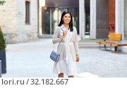 Купить «happy smiling young asian woman on city street», фото № 32182667, снято 13 июля 2019 г. (c) Syda Productions / Фотобанк Лори