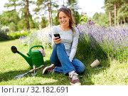 Купить «woman with smartphone and garden tools in summer», фото № 32182691, снято 12 июля 2019 г. (c) Syda Productions / Фотобанк Лори