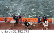 Купить «Пассажиры стоят на корме круизного парома. Столы, стулья, кушетки на палубе. Круиз на лайнере Viking Line в Балтийском море», видеоролик № 32182775, снято 17 июня 2019 г. (c) Кекяляйнен Андрей / Фотобанк Лори